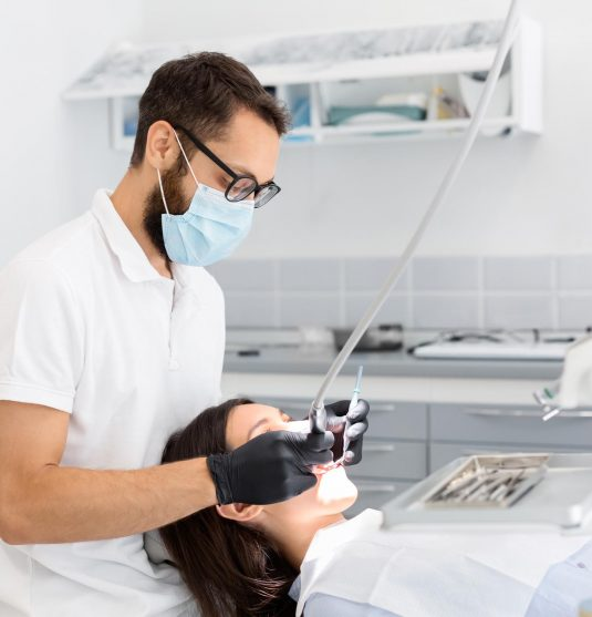 dentist-doctor-in-glasses-filling-teeth-to-female-QGHT5GS.jpg